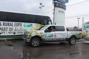 IPM 2018 Co-Chair Leon LeClair sits in the sponsored Victory Ford vehicle beside the IPM Badder Bus coach.